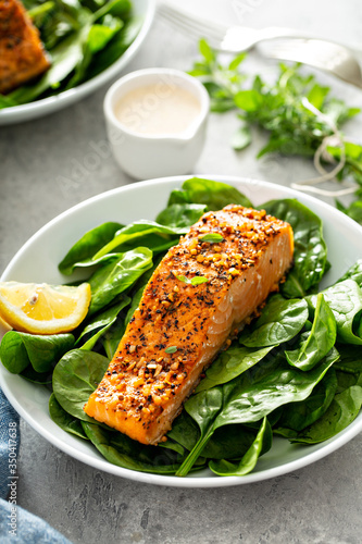 Cedar plank grilled salmon with spinach and spicy cream sauce