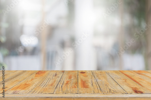 Obraz na plátně Empty wood table top and blur glass window interior restaurant banner mock up abstract background - can used for display or montage your products
