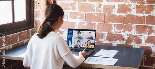 Fotomural Young Asian businesswoman work at home and virtual video conference meeting with