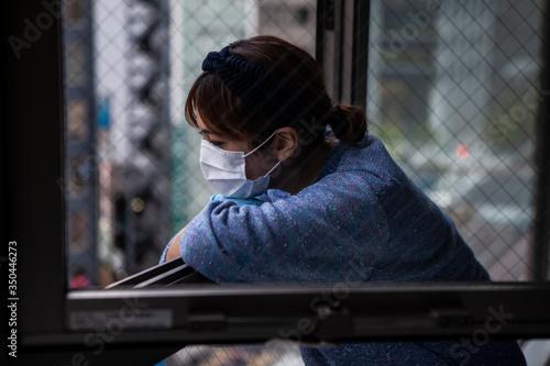 Photo 寂しそうに外を眺める、コロナウイルスで外出自粛をする女性