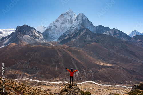 A trekker standing on rock and looking to Ama Dablam mountain peak in Dingboche фототапет