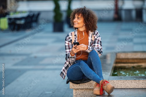 Fototapeta Young attractive mixed race woman sitting on fountain, using smart phone and enjoying music. obraz