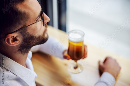 Closeup of young melancholic businessman in shirt sitting in pub next to window and looking trough it Wallpaper Mural