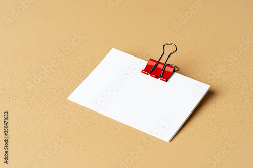 Pile of white businesscards with a clip on beige background, copy space