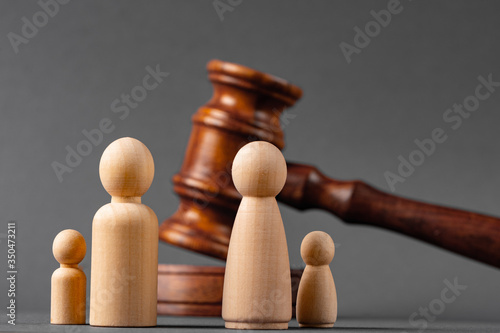 Wooden toy family and judge mallet close up. Family divorce concept