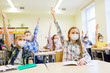 Leinwandbild Motiv education, pandemic and health concept - group of students wearing face protective medical mask for protection from virus disease raising hands at school