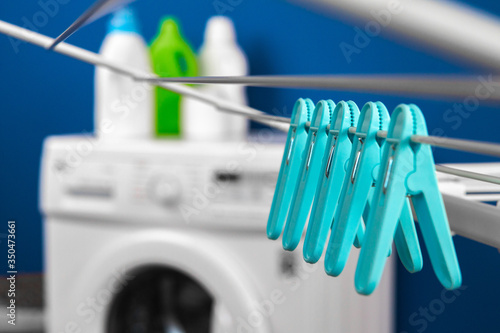 Clothes hanger rack dryer with clothespins close up against blue background