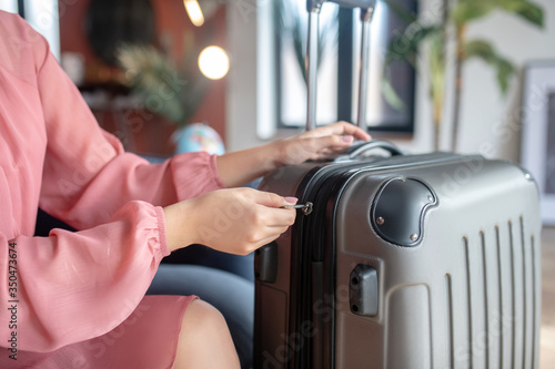 Close-up of female hands zipping her suitcase