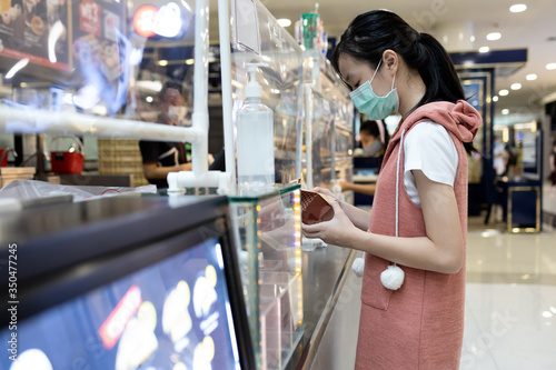 Fotografía Asian child girl in a mask,buying food at shopping mall after Coronavirus quaran