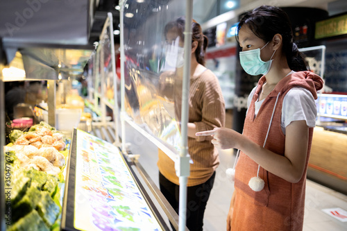 Fototapeta Asian child girl in a protective mask,ordering food in food court at the department store after Coronavirus quarantine Covid-19 with plastic shield partition,social distancing safety,new normal life obraz