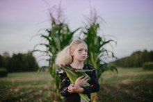Girl In A Field Holding Corn