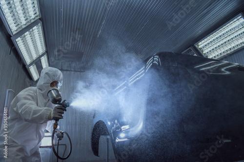 Fototapeta close up of paint spray gun, worker painting a car obraz