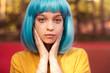 Leinwanddruck Bild - Teenager in blue wig looking at camera