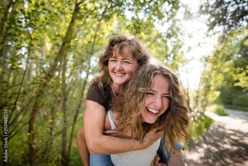 Mother enjoying piggyback ride on her daughters back Wallpaper Mural