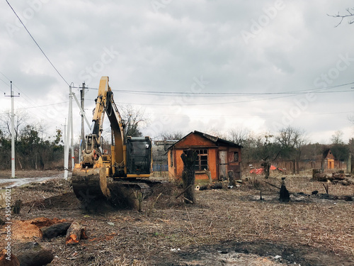 Photo Excavator uprooting trees on land in countryside