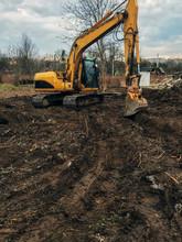 Excavator Uprooting Trees On L...