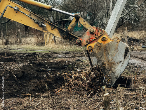 Excavator uprooting trees on land in countryside Canvas Print