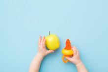 Infant Hands Holding Green App...