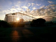 Roller Coaster Against Cloudy Sky During Sunset
