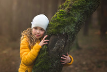 Young Girl Leaning Against The Tree In The Forest