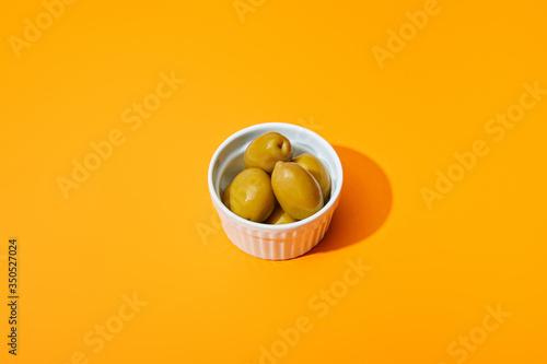 Fototapeta olives in bowl on orange colorful background obraz