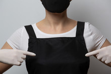 Close-up Template. The Girl In The Black Apron Points Her Fingers To Her Chest. Hands In Rubber Gloves, Face In A Mask. Cooking Safety Concept. Place For Text. Mockup. Copy Space.