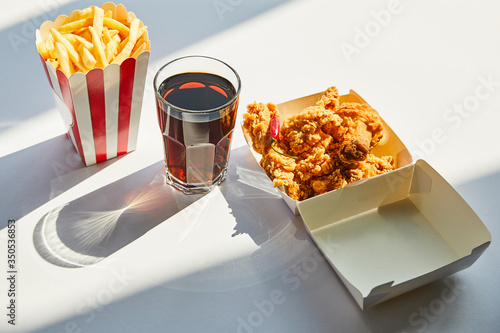 Fototapeta tasty deep fried chicken, french fries and soda in glass on white table in sunlight obraz