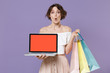 Leinwanddruck Bild - Shocked young woman in summer clothes isolated on violet background. Shopping discount sale concept. Mock up copy space. Hold package bag with purchases laptop pc computer with blank empty screen.