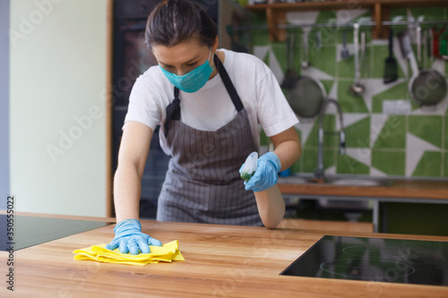 Obraz Woman in protective mask and gloves cleaning kitchen - fototapety do salonu