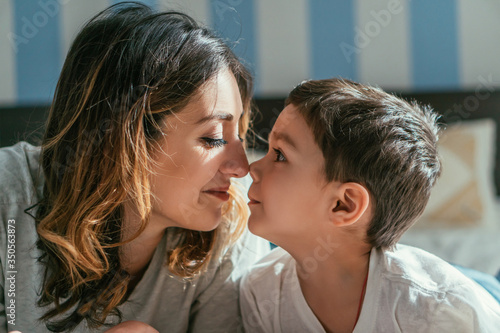 Fotografie, Obraz side view of happy mother and cute toddler son looking at each other in bedroom