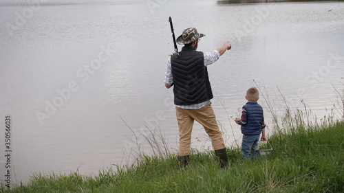 Obraz A father with a fishing rod on his shoulder standing on the edge of the shore shows his little son the lake, places where you can go fishing. Dad and son go fishing - fototapety do salonu