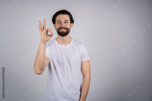 A young man with a beard in a white t-shirt standing on gray background, hand sh Wallpaper Mural