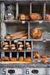 In a French bakery, close-up on wooden shelves presenting breads