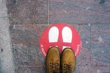 Closeup Of Red Circle With Feet In Front Of Fashion Store With Text In French Respectez Les Distances, Traduction In English : Respect The Distance,  During The Covid-19 Pandemic