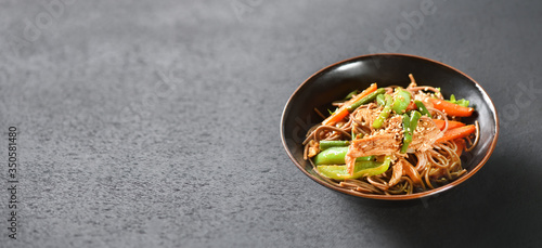 Fototapeta A bowl of wok noodles stands on a black table background with a copy space obraz