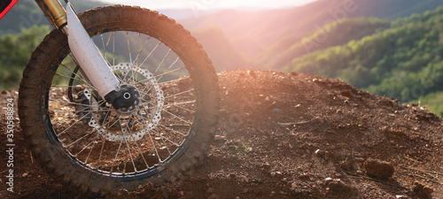 Fotografija Part of a motocross wheel on a mound, with sunrise