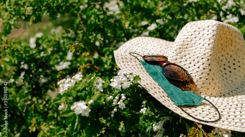 Fototapeta Summer break in new normal with Coronavirus. Canceled summer holiday, Local tourism. Lockdown vacation plans. Straw hat, sunglasses and protective face mask obraz