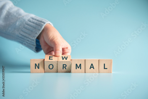 Photo Woman hand flipping wooden cubes with NEW NORMAL word