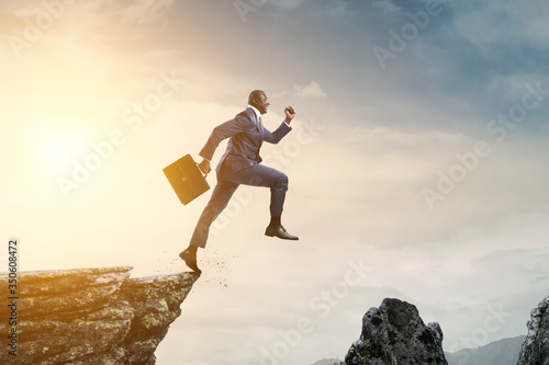 Fotografia Black businessman jumping over mountain stones