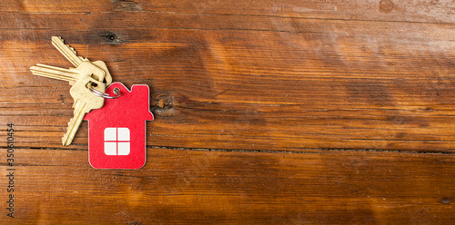Fototapeta House keys with home keyring decorated on rusty wood background, copy space. Real estate concept obraz