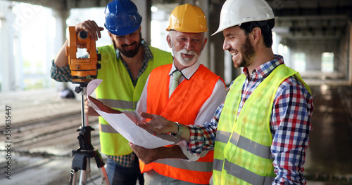Team of construction engineers, architects working on building site