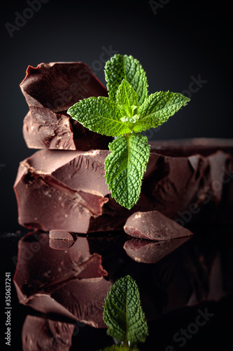 Photo Large piece of dark bitter chocolate with mint on a black reflective background