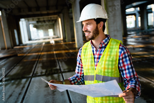 Fotografia Architect, engineer looking at blueprints in a construction site
