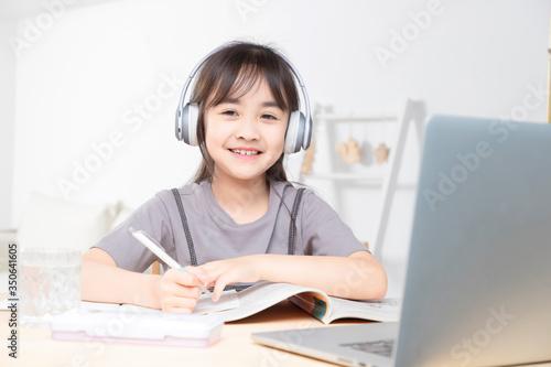 Asian little girl surfing internet at home Wallpaper Mural