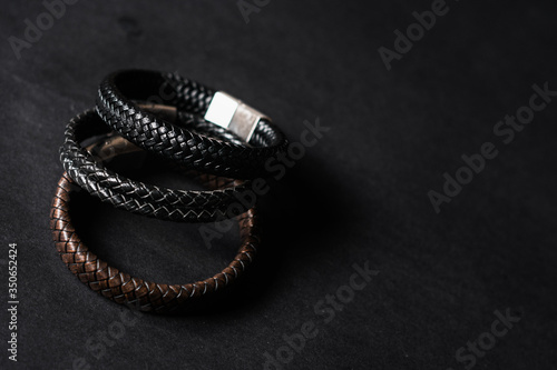 leather and silver bracelets on black background Fototapeta