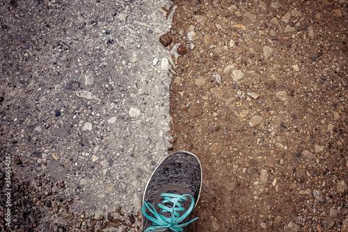 Fotografía Zapatilla sobre suelo mitad naranja terreno, mitad charco