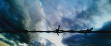 Low Angle View Of Silhouette Barb Wire Against Cloudy Sky