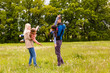 canvas print picture - young familiy are walking through a green field