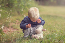 Little Boy Is Talking With Plush Sheep, Boy With Plush Toy On Green Grass