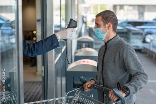 Fotografia Temperature check at a supermarket of man, grocery store with thermal imaging camera